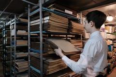 Um estudante na biblioteca ou na sala do arquivo est? procurando a informa??o Uma estudante em uma camisa branca retira um livro  fotografia de stock