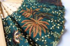 Um fã de madeira da mão no pano Javanese chamou o batik foto de stock