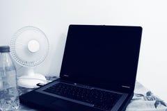 Um fã de tabela está ao lado de um portátil e de uma garrafa plástica enchidos com água foto de stock
