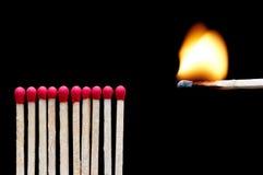Um fósforo ardente perto de outros fósforos Fotos de Stock Royalty Free