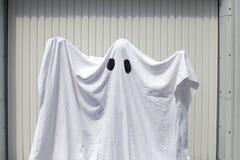 Um fantasma na frente de uma porta da garagem Fotografia de Stock Royalty Free
