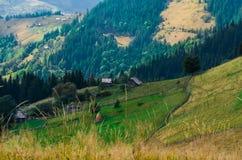Um farmer' velho; a casa de madeira de s está em uma montanha do elefante perto de um monte de feno contra o contexto de pico fotos de stock