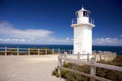 Um farol branco sobre a vista do mar imagens de stock royalty free