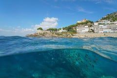 Um farol e construções em um litoral rochoso com uma escola dos peixes debaixo d'água, metade da opinião da separação acima e aba imagens de stock royalty free
