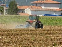 Um fazendeiro com um trator que ara a terra antes de 125 de sementeira Fotografia de Stock