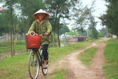 Um fazendeiro da mulher biking em casa de seu trabalho no campo de almofada Imagem de Stock