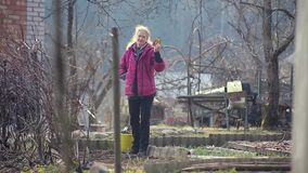 Um fazendeiro da mulher trabalha a terra com uma enxada video estoque