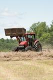 Um fazendeiro em um trator do vermelho faz feno um campo em Nova Inglaterra Imagens de Stock Royalty Free