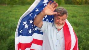 Um fazendeiro idoso com uma bandeira americana em seus ombros que acenam sua mão, adeus ou cumprimentando Dia patriótico vídeos de arquivo