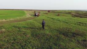 Um fazendeiro maduro olha um campo verde fresco ap?s o inverno, faz planos para colher e preparar-se para semear filme