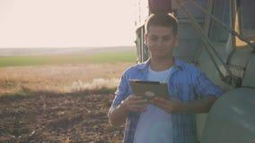 Um fazendeiro pensativo está trabalhando no campo Usa uma tabuleta, está perto da engenharia agrícola vídeos de arquivo