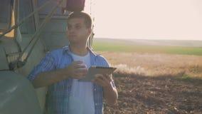 Um fazendeiro pensativo está trabalhando no campo Usa uma tabuleta, está perto da engenharia agrícola video estoque