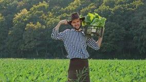 Um fazendeiro que leva uma caixa de couves em seu ombro filme