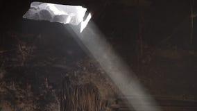 Um feixe de luz fumarento através de um furo no telhado vídeos de arquivo
