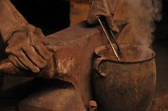 Um ferreiro que refrigera uma ferradura em um potenciômetro Imagem de Stock Royalty Free