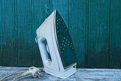 Um ferro bonde sujo branco em uma tabela de madeira contra uma parede verde foto de stock