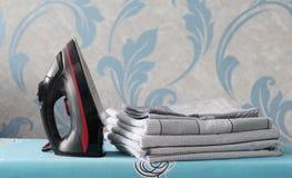 Um ferro preto está na tábua de passar a ferro Perto de uma pilha do roupa de cama imagens de stock
