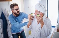 Um filho adulto do moderno e um pai superior no banheiro dentro em casa, tendo o divertimento foto de stock royalty free