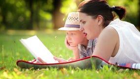 Um filho com seu mum que encontra-se no parque na tampa que lê um livro filme
