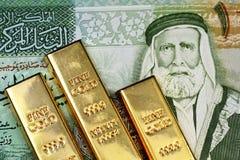 Um fim acima da imagem de um dinar jordano com as barras de ouro pequenas foto de stock
