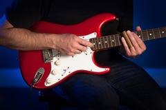 Um fim acima da opinião um homem que joga uma guitarra elétrica vermelha e branca foto de stock royalty free