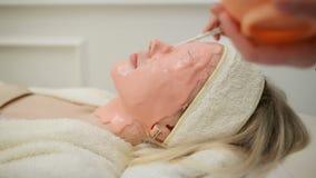 Um fim acima da vista da cara da mulher com m?scara cor-de-rosa Esteticista que limpa a m?scara facial casca Cuidados com a pele  video estoque
