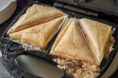 Um fim acima da vista de um sanduíche brindado em um fabricante brindado do sanduíche Imagem de Stock