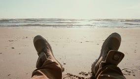 Um fim acima das botas de uma pessoa que encontra-se em um Sandy Beach que aprecia a vista da água vídeos de arquivo