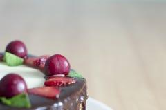 Um fim acima do bolo de chocolate com cerejas, morangos, chocol Fotos de Stock