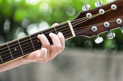 Um fim acima dos dedos das mulheres que jogam a guitarra Foto de Stock