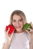 Um fim acima dos jovens e da mulher de sorriso que está guardando pimentas de sino vermelhas e verdes Dieta saudável e vitaminas  Imagens de Stock
