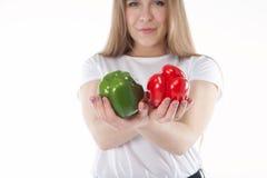Um fim acima dos jovens e da mulher de sorriso que está guardando pimentas de sino vermelhas e verdes Dieta saudável e vitaminas  Fotos de Stock