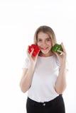 Um fim acima dos jovens e da mulher de sorriso que está guardando pimentas de sino vermelhas e verdes Dieta saudável e vitaminas  Fotos de Stock Royalty Free