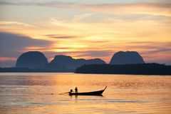 Um fisheman no barco do longtail contra o fundo do nascer do sol fotografia de stock royalty free