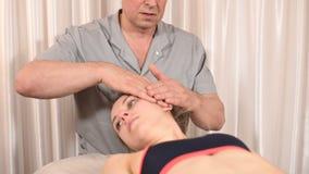 Um fisioterapeuta masculino faz a um bem-estar o procedimento manual para um paciente da moça Osteopathy e não-tradicional vídeos de arquivo