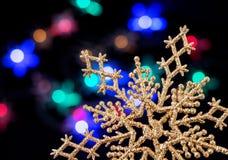 Um floco de neve dourado na perspectiva das luzes de uma festão do Natal fotos de stock royalty free