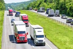 Um fluxo pesado de 18 veículos com rodas salpicou com carros e SUVs rola para baixo uma estrada nacional de Tennessee fotos de stock