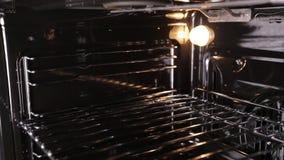 Um fogão de gás moderno com um forno em que uma luz se está queimando, uma vista para dentro, um close-up filme