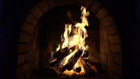 Um fogo queima-se em uma chaminé do tijolo, mantém-se morno vídeos de arquivo