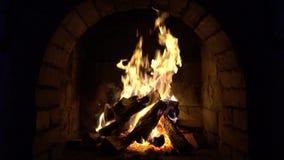 Um fogo queima-se em uma chaminé do tijolo, mantém-se morno filme