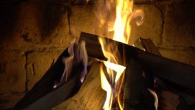 Um fogo queima-se em uma chaminé do tijolo, mantém-se morno video estoque