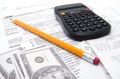Um formulário de imposto com dinheiro do lápis e a calculadora preta Foto de Stock Royalty Free