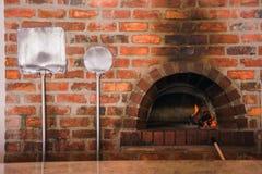 Um forno da pizza do tijolo vermelho e duas cascas da pizza imagens de stock royalty free