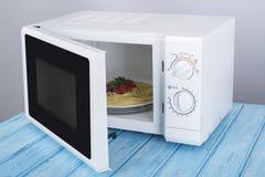 Um forno micro-ondas branco novo, em uma superfície de madeira azul para aquecer-se Imagem de Stock
