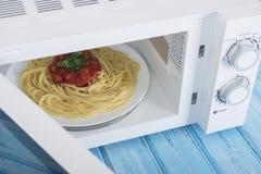 Um forno micro-ondas branco novo, em uma superfície de madeira azul para aquecer-se Foto de Stock Royalty Free