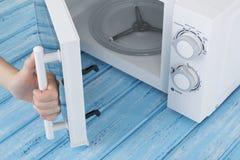 Um forno micro-ondas branco novo, em uma superfície de madeira azul para aquecer-se Fotos de Stock Royalty Free