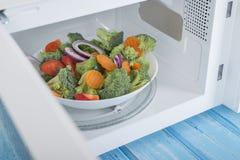 Um forno micro-ondas branco novo, em uma superfície de madeira azul para aquecer-se Fotografia de Stock Royalty Free