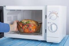 Um forno micro-ondas branco novo, em uma superfície de madeira azul para aquecer-se Imagem de Stock Royalty Free