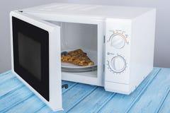 Um forno micro-ondas branco novo, em uma superfície de madeira azul para aquecer-se Fotos de Stock