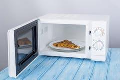 Um forno micro-ondas branco novo, em uma superfície de madeira azul para aquecer-se Fotografia de Stock